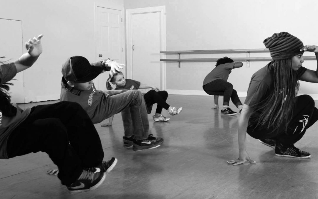 Children perform dance moves together in the dance studio.
