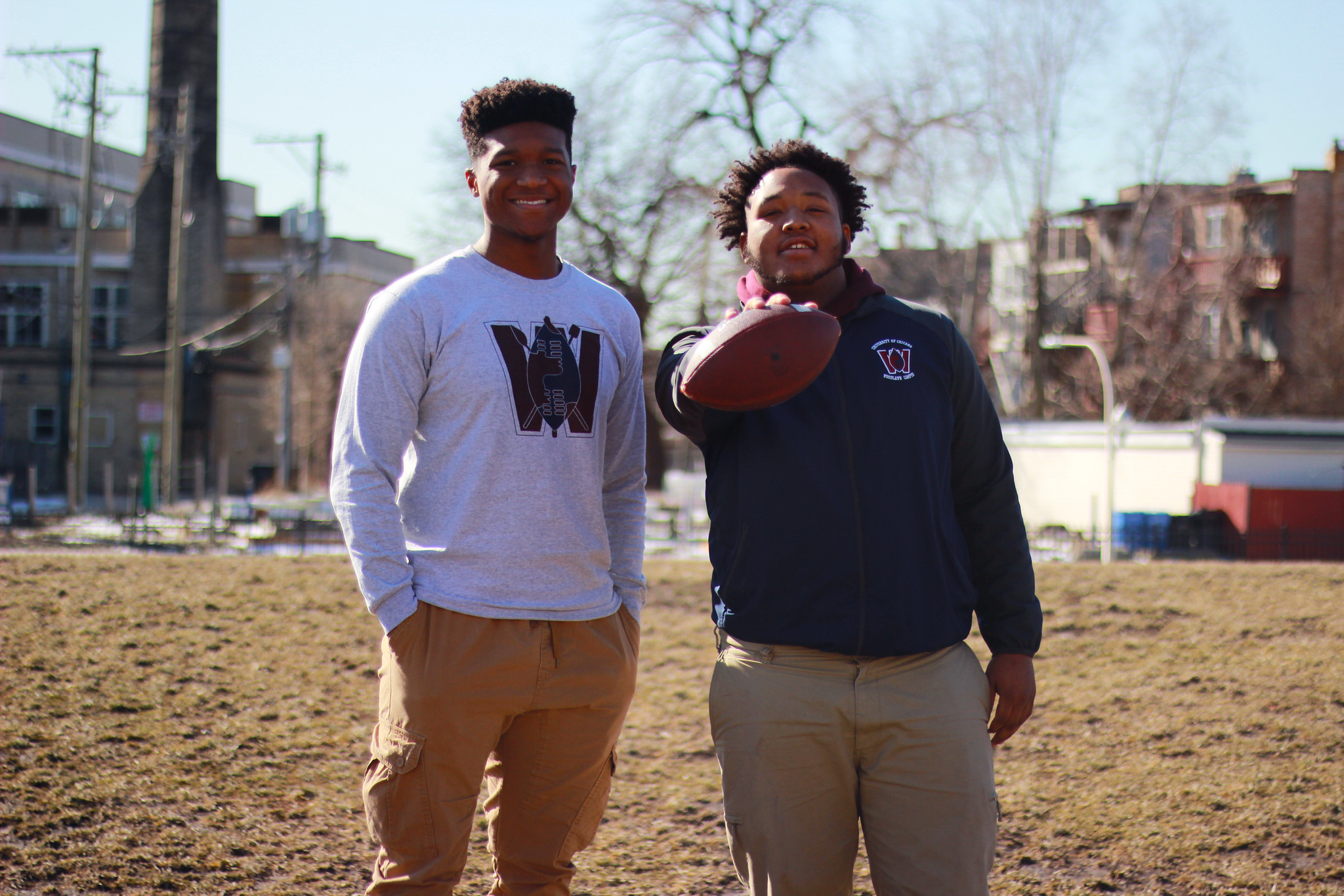 Julien and Terrance stand side by side outside their campus building. Terrance holds a football.